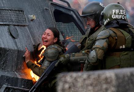 MUJER ANTIDISTURBIOS EN LLAMAS DURANTE LAS PROTESTAS EN SANTIAGO DE CHILE